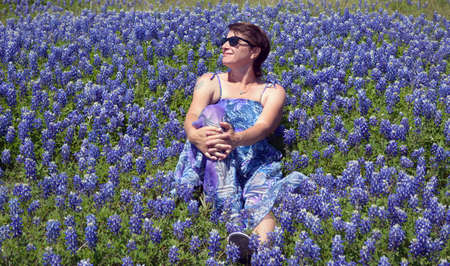 bluebonnet: A women in a purple dress and sunglasses sitting in bluebonnet flowers with her head to the side.