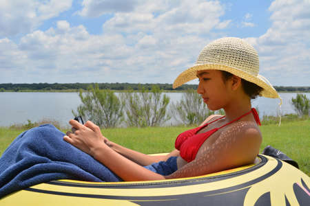 fifteen year old: Beautiful Young girl in a swimsuit texting next to a lake Stock Photo