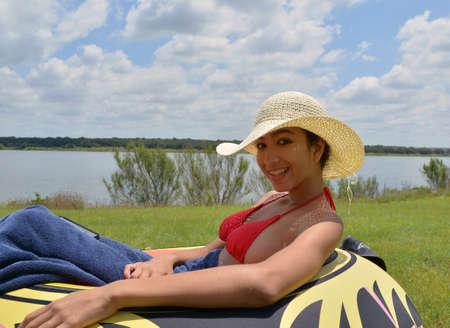 fifteen year old: Smiling teenage girl sitting on an innertube beside a lake