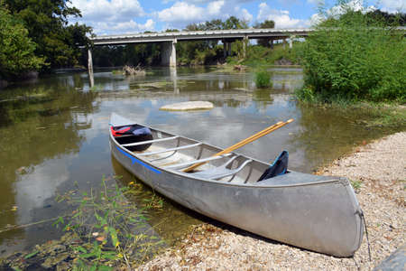 punting: Metal canoe on the beach of San Gabriel River in Texas Stock Photo