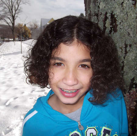 michigan snow: Close up of the face of a tan curly haired child with braces