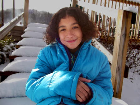 michigan snow: Curly haired mixed race child sitting on snowy steps