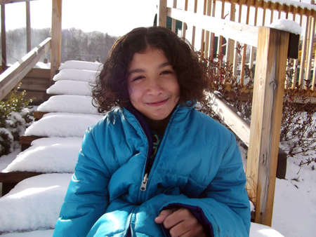 smile girl: Child with curly hair sitting on a snow covered stairway