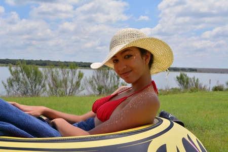 inner tube: Happy young ethnic girl in a large hat laying on an inner tube