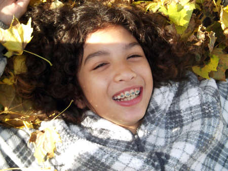 Close up of Smiling child with braces laying in Leaves Stock fotó