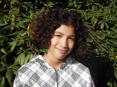 softly: Mixed Race child smiling softly hiding her braces Stock Photo