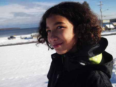 preteen girl: Preteen Girl smiling in the winter sun on the banks of Lake Superior Stock Photo
