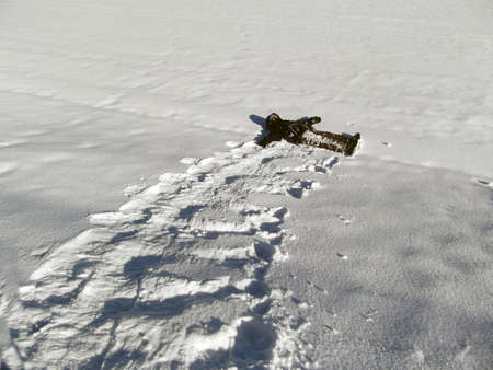 Child in winter clothing rolling down a snowy hill