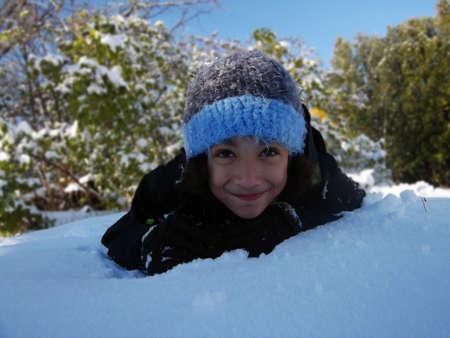 agachado: Close up de eludir hijo fuera del sol de invierno en la nieve