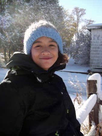chicas sonriendo: ni�a preadolescente en ropa de invierno apart�ndose del sol brillante de invierno