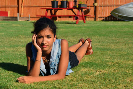 mixed race girl: Beautiful mixed race girl laying on the grass in the sun Stock Photo