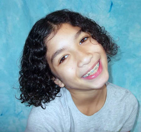 Child with curly hair with her head cocked sideways