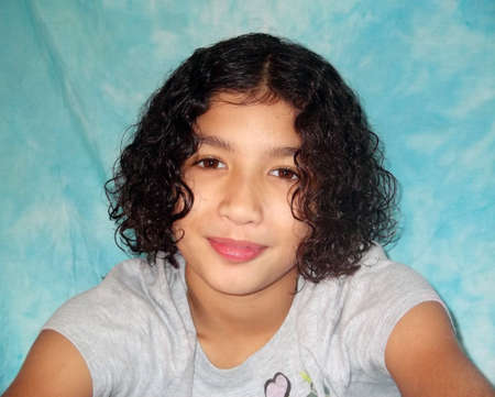 Head and shoulders of curly haired ethnic girl