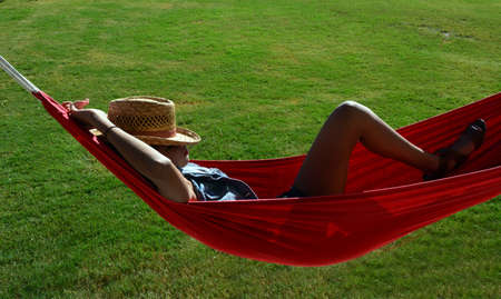 Teen girl laying in hammock with face coverd by a hat 版權商用圖片