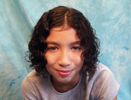 Curly haired girl head and shoulders portrait Banco de Imagens