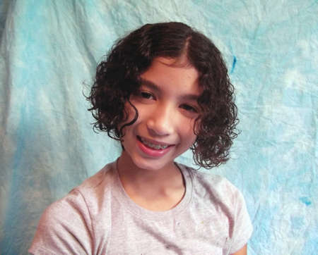 Curly haired child in braces Banco de Imagens