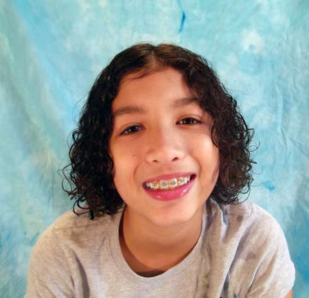 Studio shot of curly haired child in braces