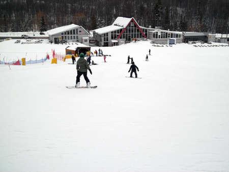 michigan snow: Children snowboarding down a small hill Stock Photo