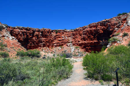 Large sink hole with red cliffs in the desert