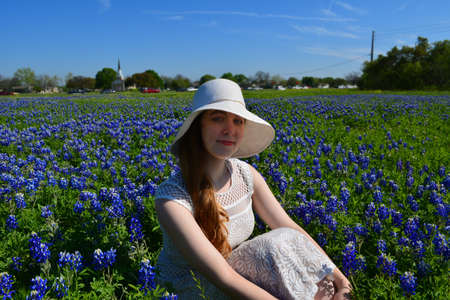 Beautiful girl in white bonnet sitting in a field of Texas Bluebonnet wildflowers 스톡 콘텐츠 - 100897244
