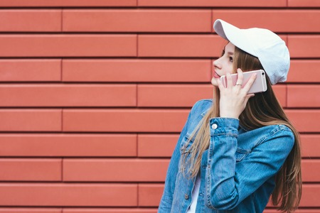 Stylish blonde girl in a denim jacket and cap talks by phone on a red background. A young woman uses a mobile phone hipster