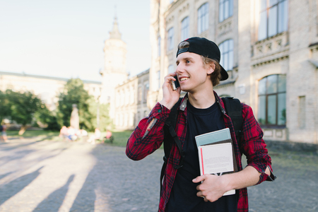 A student in a red shirt, with books in his hands, talks on a mobile phone with his friends on the background of the university and smiles.