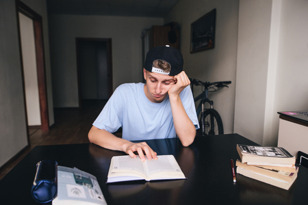 A sad student is reluctant to read a book in his room. Doing homework. Teaching at home