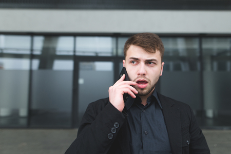 A street portrait of a young serious man with a beard that communicates on a mobile phone against a dark wall