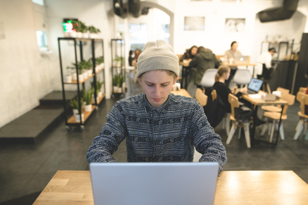 Concealed Hipsters Sit At The Table In A Cozy Cafe And Work On