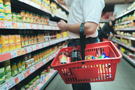 A man with a red basket for products chooses goods in a supermarket. Purchasing products at the store. Stock Photo