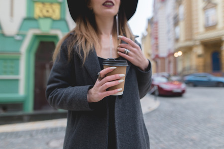 A stylish woman holds a cup of coffee or tea in her hands. Hot drink in the hands of a beautiful woman. Hands close-up and in focus.