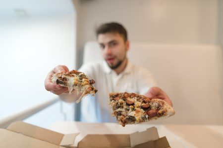 The man holds two pieces of pizza in his hands and sends them to the camera. A man offers a pizza. A delicious pizza in the hands of a guy. Zdjęcie Seryjne