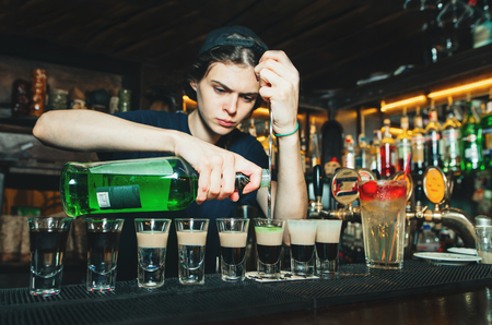 Girl bartender creates alcoholic show at the bar. The barman pours alcohol into glasses with shots