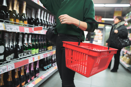 A woman with a red shopping bag chooses alcohol in a supermarket. Selection of products in the supermarket. The choice of wine in the store