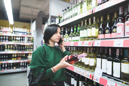 A girl with a bottle of wine in her hands speaks by phone. A girl with a phone purchases in a supermarket. Shopping in a supermarket with a phone