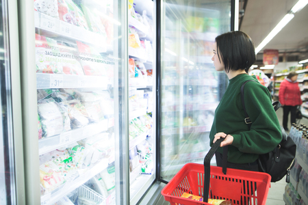 The girl opens a fridge for frozen foods in the supermarket. The girl is shopping at the supermarket