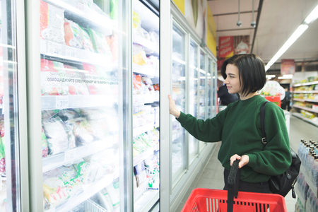 The buyer near the refrigerator in the supermarket. A beautiful girl buys food at a supermarket. The buyer selects the goods in the store Banco de Imagens