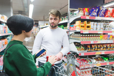 Young couple standing at the supermarket sweets and talking. Family shopping at a supermarket