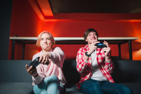 Emotional young people are sitting on the couch and playing games on the console. A man and a girl with gamepads in their hands play home games. Focus on the joysticks.