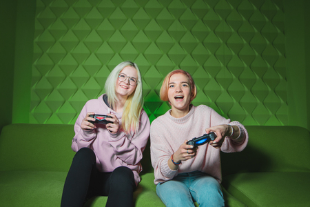 Two happy girls blond girls playing console games on a green background. Positive friends with gamepads in their hands play video games and smile.