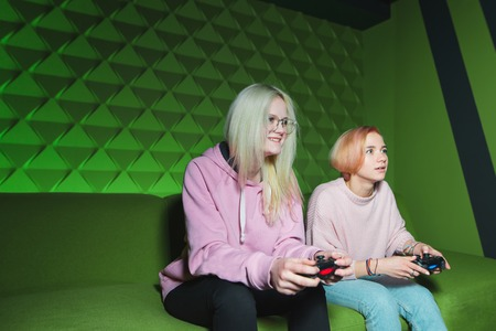 Blond women play console video games in a room with a green interior. Girlfriends have fun playing games on gamepads. Stock Photo