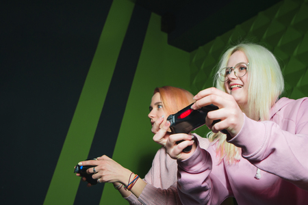 Gamepads in female hands close up. Emotional girlfriends with joysticks in their hands sit on the sofa on a green background and play video games.