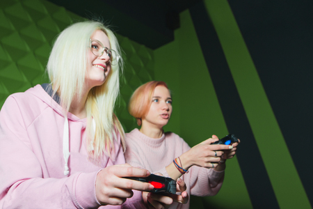 Happy girls play video games on the console. Gamepads in the hands of women close up and in focus. Stock Photo