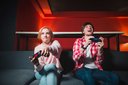 Emotional young couple sitting at home on the couch and playing video games on the console. A man and a girl with gamepads in their hands actively play games. Gamer concept Stock Photo