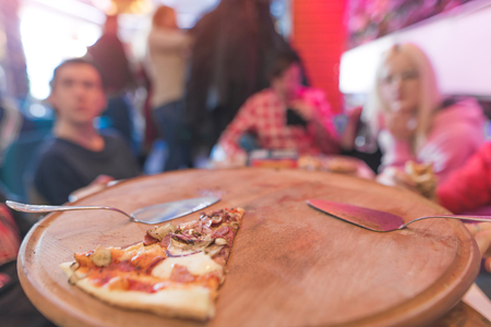 The last piece of pizza on the background of a group of friends. A piece of pizza on the background of young people. Students sit in a pizzeria and eat pizza. Reklamní fotografie