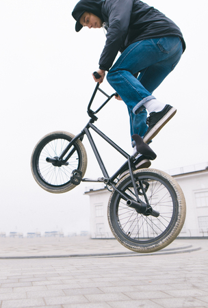BMX freestyle close up. A young man makes stunts on a BMX bike