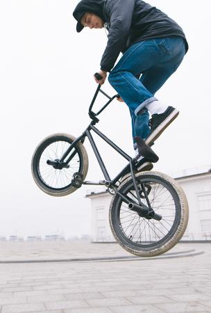 BMX freestyle close up. A young man makes stunts on a BMX bike