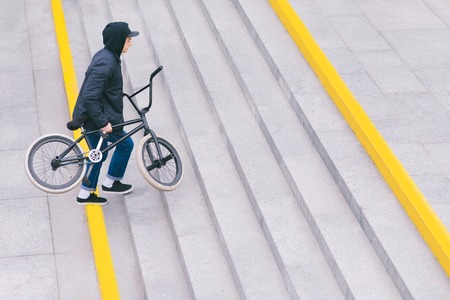 Walk around the city with BMX by bike. BMX concept. The man goes upstairs. Top view. Copyspace Banque d'images