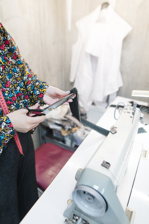 Seamstress standing at the workplace and cuts fabric with scissors. Фото со стока