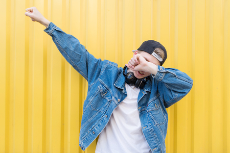 Young man throws dab on the background of a yellow wall Banque d'images - 100567643
